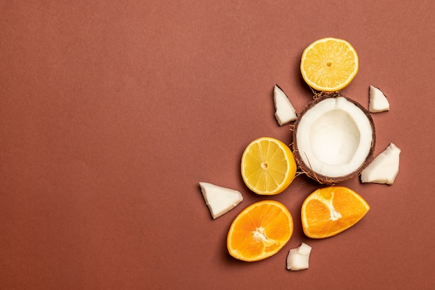 Свежие экзотические фрукты: ананас, кокос, апельсин, лимон на коричневом фоне.