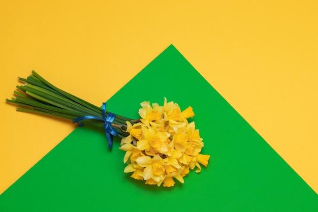 テキスト用のスペースと背景に女性の手で新鮮な黄色の水仙の花束