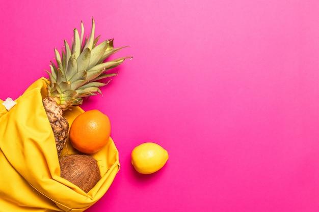 Композиция из различных свежих экзотических фруктов с желтой хлопковой сумкой на розовом фоне