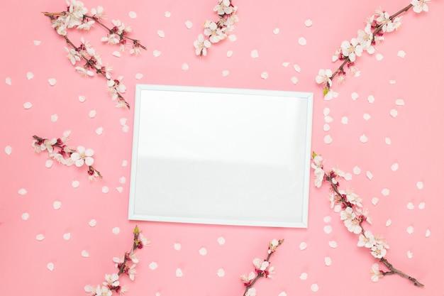 花の組成フォトフレーム、ピンクの背景の花。