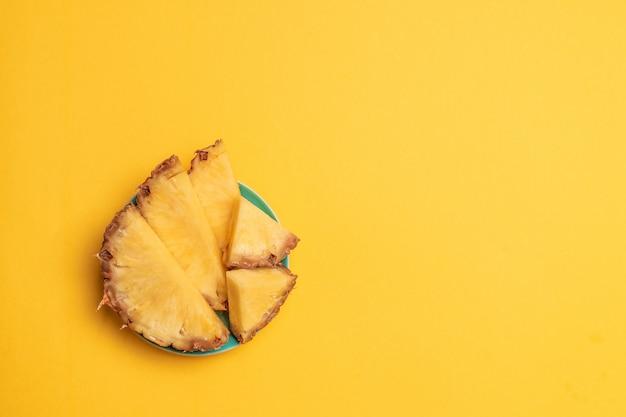 フルーツの背景夏の果物パイナップルスライスグリーンプレート。フラットレイアウト、上面図、コピースペース