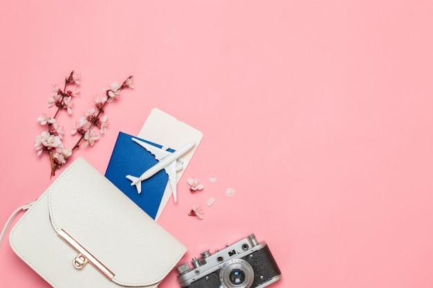 飛行機のおもちゃモデル、古いカメラ、チケット、パスポート、ピンクの背景のハンドバッグ。