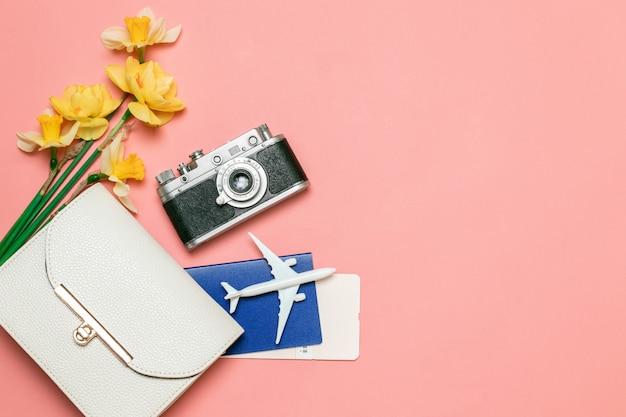 旅行の概念飛行機のおもちゃモデル、古いカメラ、チケット、パスポート、ピンクの背景のハンドバッグ。フラット横たわっていた、上面図。