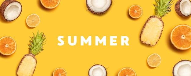 熱帯の抽象的な背景。パイナップル、レモン、オレンジ、黄色の背景にココナッツ。