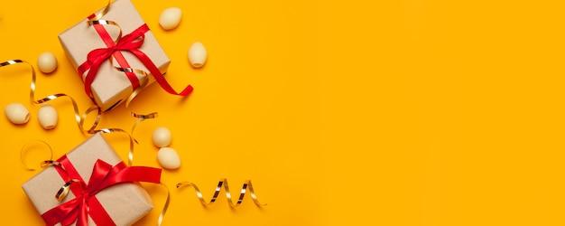 赤いリボンの弓と金の装飾が施された明るいクラフトサプライズギフトボックス、コピースペース平面図