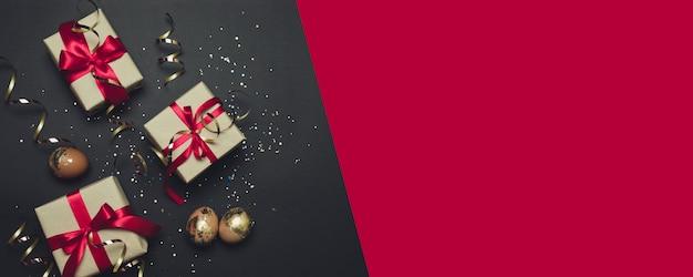 Пасхальные подарки с красными лентами и блестками на темном фоне