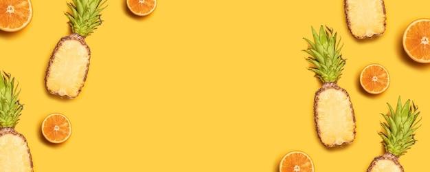 明るい夏のフルーツコンポジション。黄色の背景にジューシーなトロピカルフルーツ