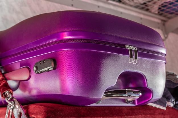 列車の車の棚の上のポリカーボネートのスーツケース