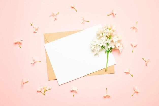 モックアップホワイトグリーティングカードと明るい背景にライラックの枝を持つ封筒