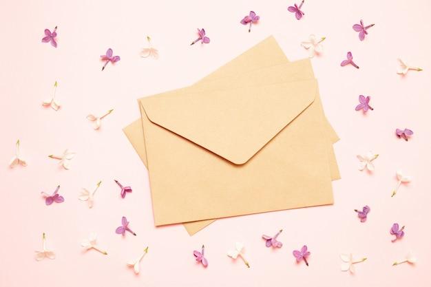 テーブルの上の空白の紙と紫色のライラックの花。素朴なスタイル
