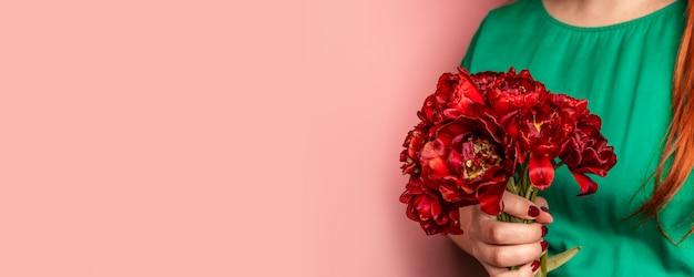 Рука женщины при маникюр держа цветки тюльпанов на розовой предпосылке.