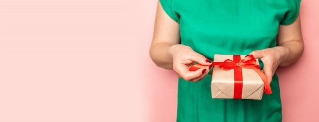 お祝いの言葉のギフトボックスを持つ女性の手。ギフト開梱