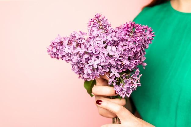 Женщина прячет голову в букет сиреневых цветов