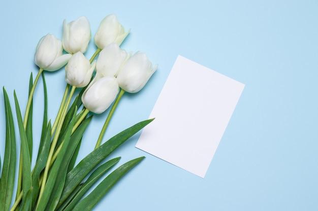 Красивый букет и карточка тюльпанов для текста на голубом взгляд сверху предпосылки. день матери