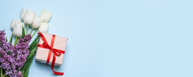 Вид сверху букет белых тюльпанов, подарочная коробка с красной лентой и веточкой сирени на синем фоне