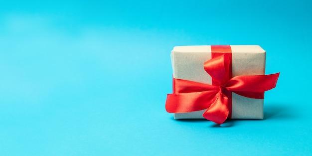 青色の背景に赤いリボンの弓とサプライズギフトラップ。お誕生日おめでとうございます