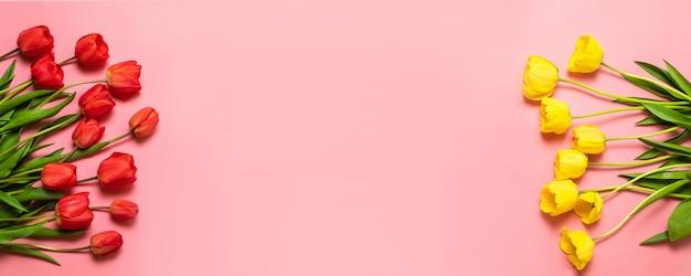 春の花ピンクの背景に分離された色のチューリップの花の花束。