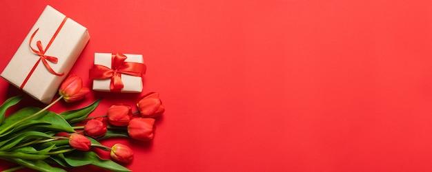 赤いチューリップと赤い背景の赤いリボンとギフトボックスの束。