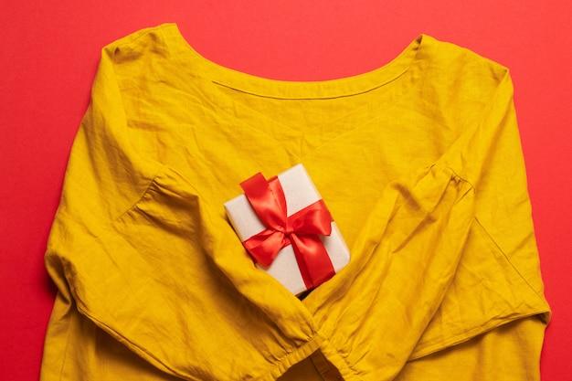 Женская желтая хлопковая блузка и и подарочная коробка на красном фоне.