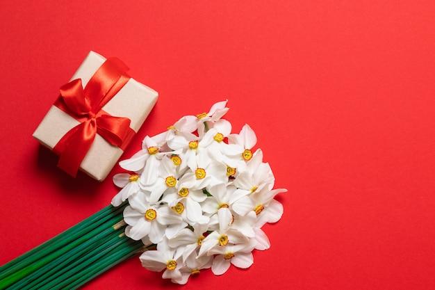 Весенняя композиция. букет из красных цветов и подарочной коробке на красном фоне.