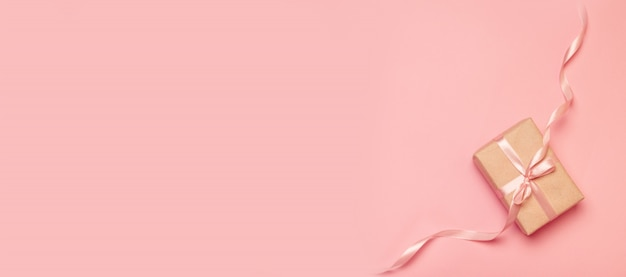 休日のバナー。ピンクのリボンで飾られたギフトクラフト紙として包まれた贈り物の平面図