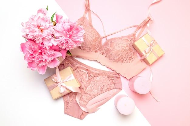 Женский элегантный розовый кружевной бюстгальтер и трусики, цветы розовые свечи, букет красивых пионов, подарки