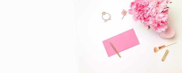 Вид сверху на розовый бумажный конверт с золотой ручкой, женские аксессуары, букет розовых пионов, свечи на белом
