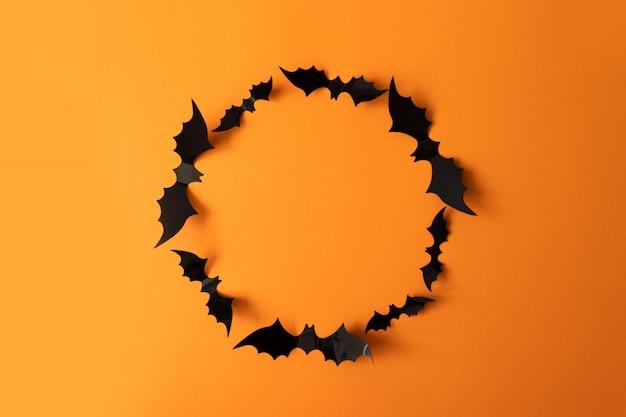 オレンジ色の表面に黒のバットフレームとハロウィーンの休日の概念
