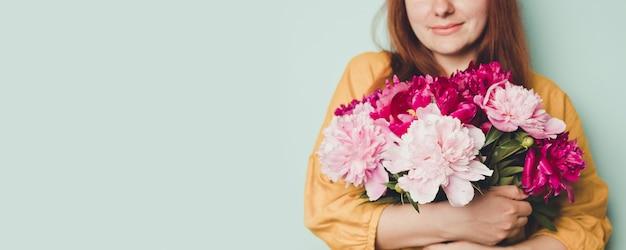香り高い牡丹と美しい花束を持っている女性の手