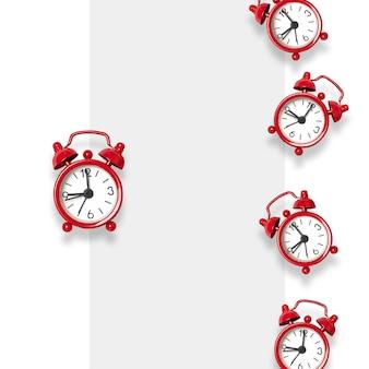 Плоская композиция из красных будильников на сером