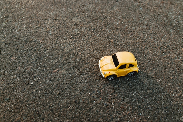 夏の日光のビーチで黄色のおもちゃの車。