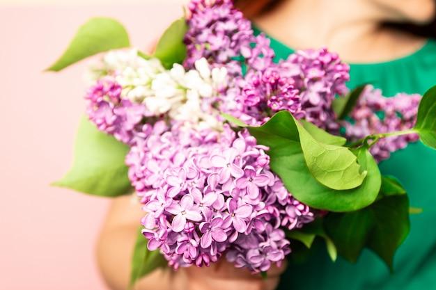 ピンクのライラックの花束を保持している緑のドレスの女の子