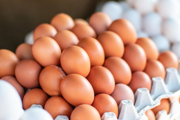 店または市場のカウンターにあるさまざまなサイズの鶏の卵の盛り合わせ。