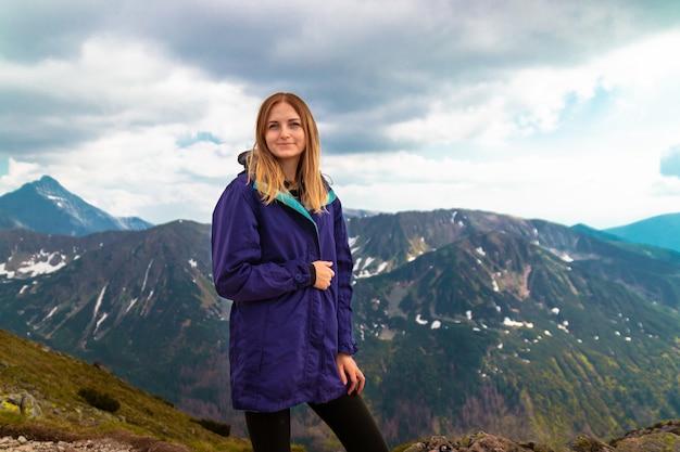 観光アドベンチャー。暖かい灰色のセーターを着た金髪の少女は、山の頂上に登り、カメラマンのカメラを見ています。