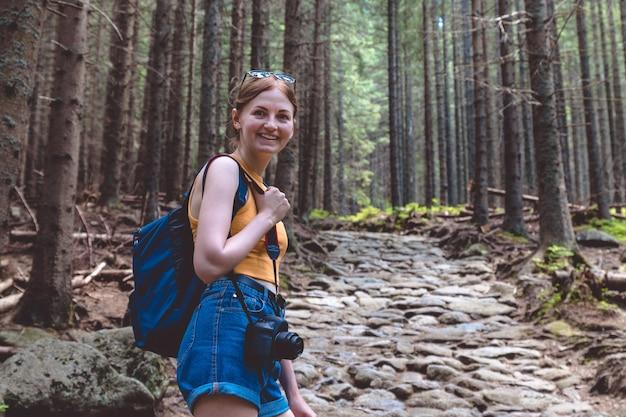 バックパックとショートパンツで女性観光客が森を旅します。