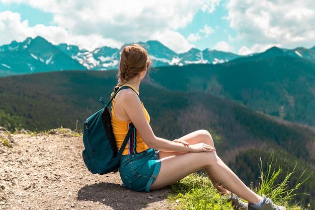 バックパックとメガネの金髪のかわいい女の子は山の上に座って、晴れた日に山の美しい丘を楽しんでいます。