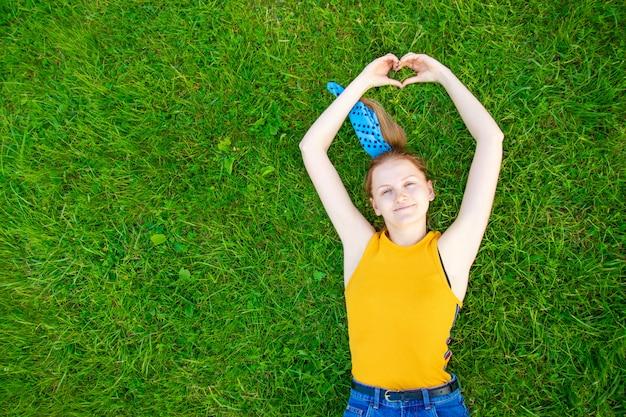 リラクゼーションと瞑想のコンセプト。うれしそうな笑顔の女の子は草の上にあります。