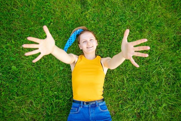 うれしそうな笑顔の女の子は草の上にあります。