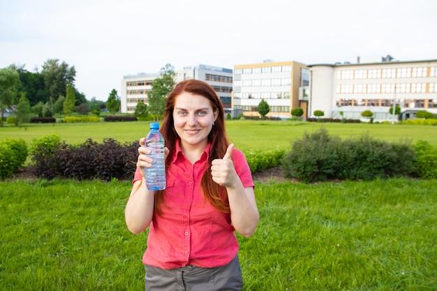 Молодая девушка в яркой летней одежде держит пластиковую бутылку воды