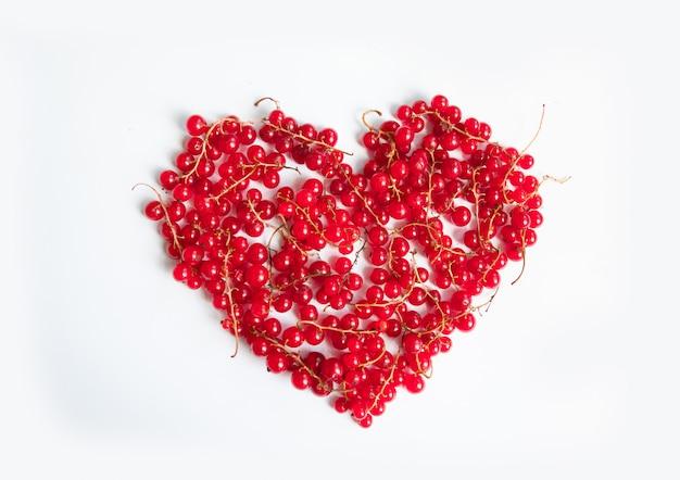 テキストのコピースペースで白い背景にハート形の赤いベリーフルーツ。