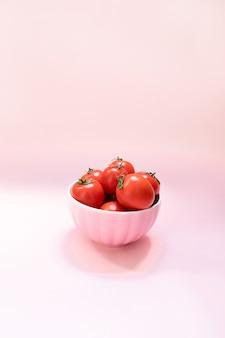 ピンクの背景に熟した赤いトマトとピンクのセラミックボウル。健康的な食事ビタミンバイオ食品
