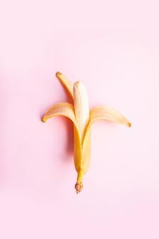 夏のビタミン。フラットコンポジション甘いは、テキストのコピースペースとピンクの背景にバナナを開きました。