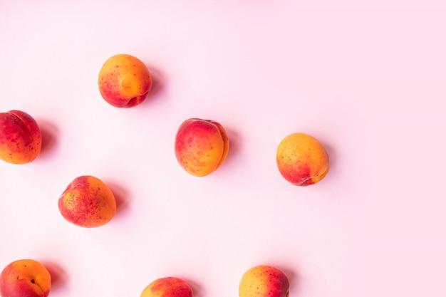 Плоская композиция спелых вкусных персиков с красной стороны на розовом фоне.