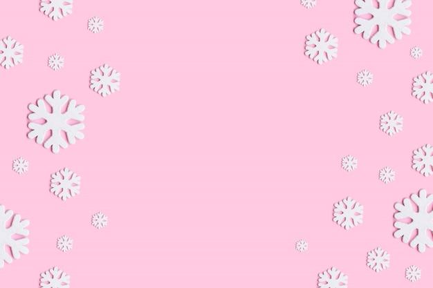クリスマス、冬、新年のコンセプト。パステルピンクの背景に雪の冬の組成。
