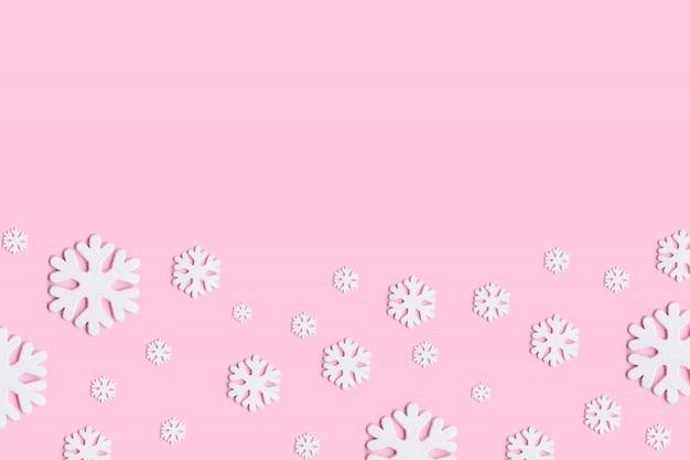 ピンクの背景に白いクリスマス雪の装飾。