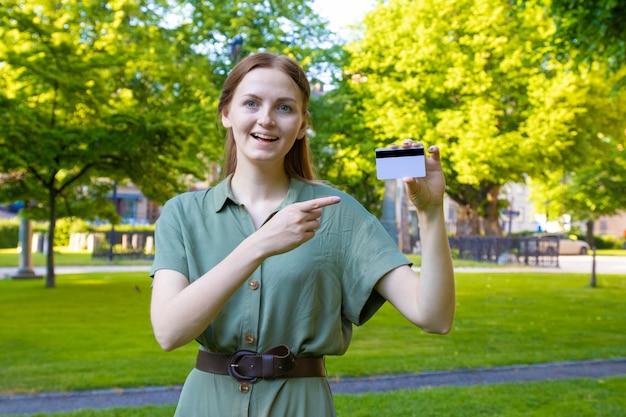 公園でクレジットカードを持つブロンドの女の子