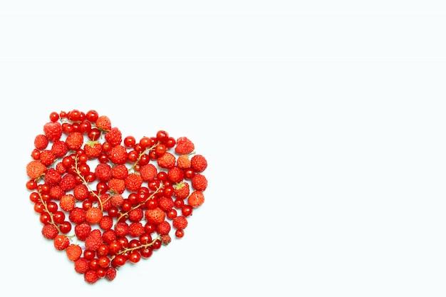 ハート形の白い背景の上のベリー果実の盛り合わせ。