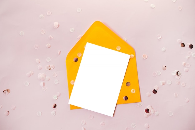 Творческая композиция с бумажным бланком и желтым конвертом на черном столе над головой для свадебной планировки