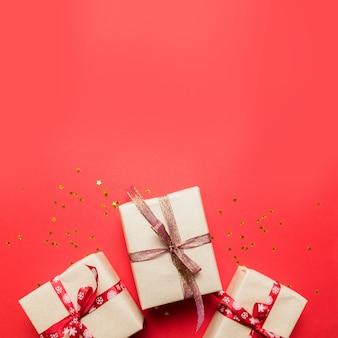 赤いテーブルトップビューでギフトまたはプレゼントボックスと星の紙吹雪。誕生日、母の日、結婚式の創造的な構成。