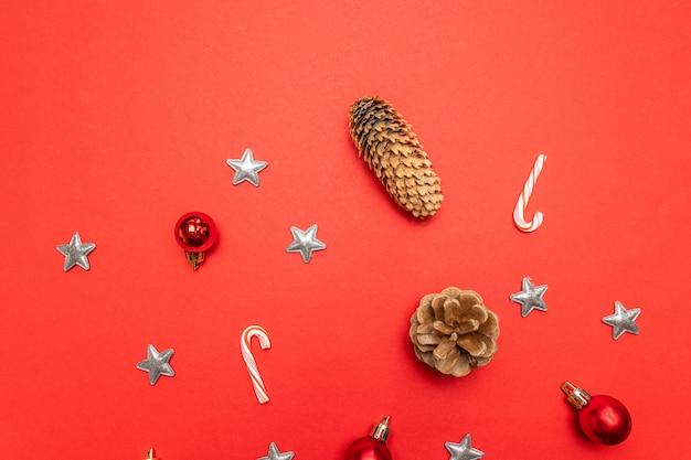Граница из красного с шишками, рождественские украшения серебряные звезды, леденцы на красном фоне.